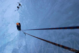 Ice climber following on double ropes