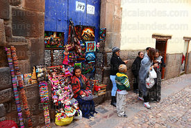 Woman selling souvenirs in doorway, Cusco, Peru