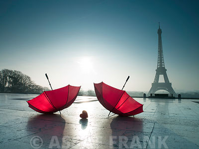 Two umbrellas next to the Eiffel tower