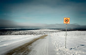 Speed limit roadsign on icy road