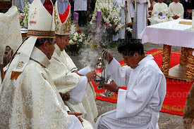 Bishop of Puno Jorge Carrion Pablisch putting incense into silver incense burner at start of central mass, Virgen de la Candelaria festival, Puno, Peru