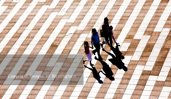 A family walking from Paradise Forum across the bridge to Centenary Square, Birmingham, West Midlands.