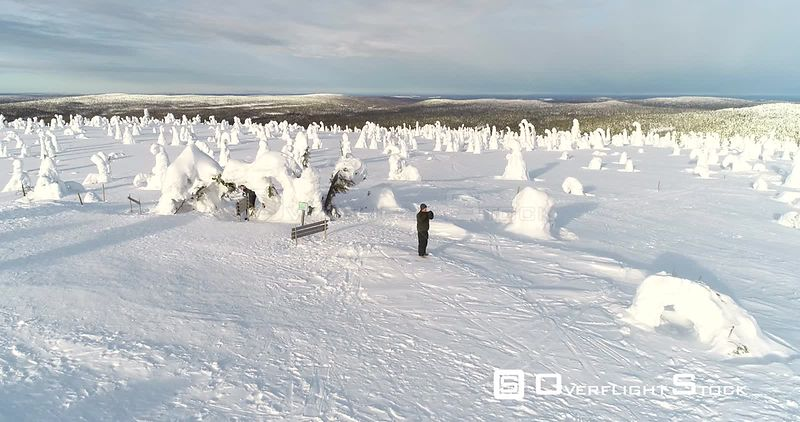 Hiking, Mountain, Aerial Vertigo Effect View Towards a Man Taking Pictures on the Top of a Fjeld Tunturi, Full of Snow Covered Trees, Riisitunturi National Park, Lapland, Finland