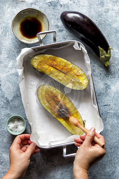 Hands brushing eggplants with olive oil.Preparing eggplant for roasting
