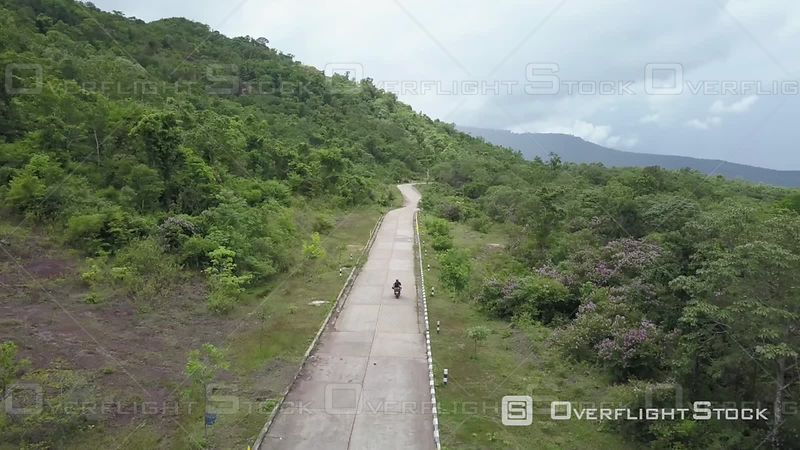 Aerial view of a motorbike filmed by drone on a country road nearby Pakse, Laos