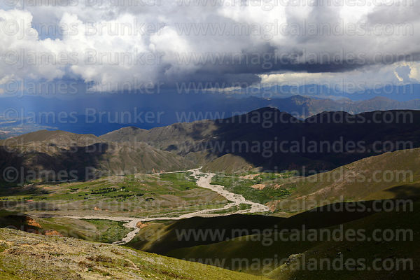 View looking down Calderillas Valley towards thunderstorm in distance over Concepcion Valley, Cordillera de Sama Biological Reserve, Bolivia