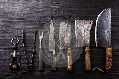Vintage Butcher meat cleavers, corkscrew and tongs on dark burned wooden background