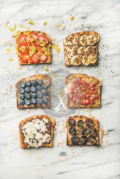 Flat-lay of vegan whole grain toasts with fruit, seeds, nuts