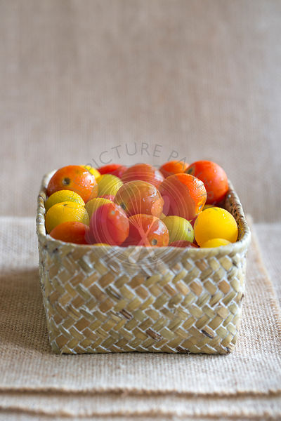 juicy red and yellow cherry tomatoes in woven basket against cream cloth background