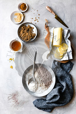 Flour, butter, sugar, honey ingredients on a work surface