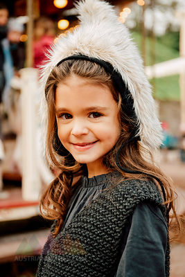 Portrait of smiling little girl wearing fur hat