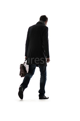 A silhouette of a mystery man in a big coat, walking away – shot from low level.