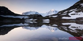Monte rosa mountain range reflected in Riffelsee lake at sunrise