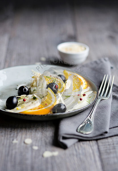 Fennel salad with black olives, orange and almond flakes. Top view