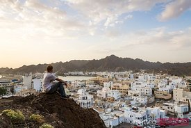 Oman, Muscat. Tourist looking at Mutrah old town