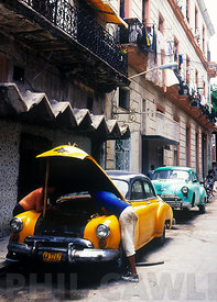 Yellow car with the hood open bieng repaired on the street in Havana Cuba