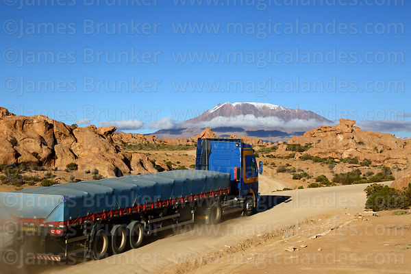 Truck on Route 701 driving past eroded volcanic rock formations, Cerro Caquella volcano in background, Nor Lípez Province, Bolivia
