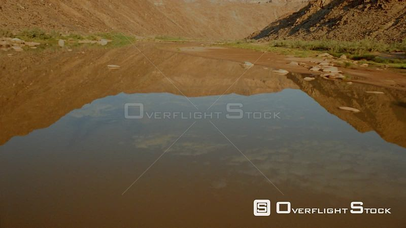 Aerial flying up river with green vegetation on riverbank and mountains and cloudy sky reflected in water Fish River Canyon Namibia
