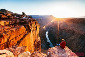 Tourist on the edge of the Grand Canyon at sunrise, USA