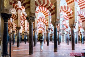 Woman walking inside the Mezquita of Cordoba, Spain