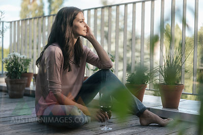 Woman with glass of red wine relaxing on balcony