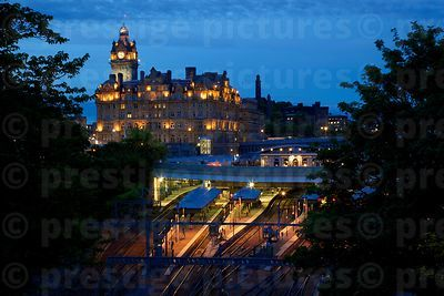 The lights of The Balmoral Hotel and Waverley Station against a deep Blue evening Sky