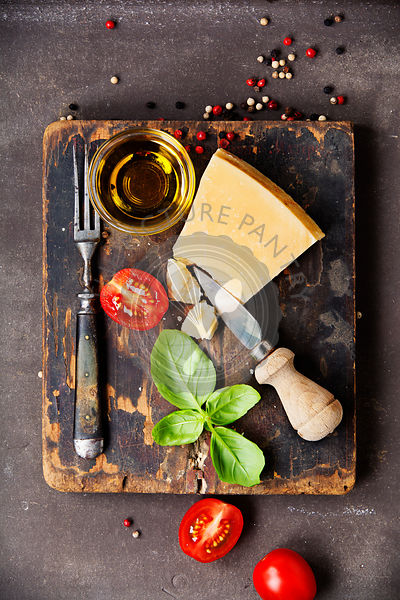 Fresh food ingredients for italian cuisine (Parmigiano, tomato, basil, olive oil) on rustic background. Top view