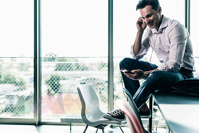 Businessman in office sitting on desk, using smartphone