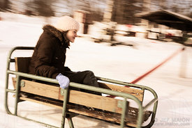 Young girl on moving sledge on snow