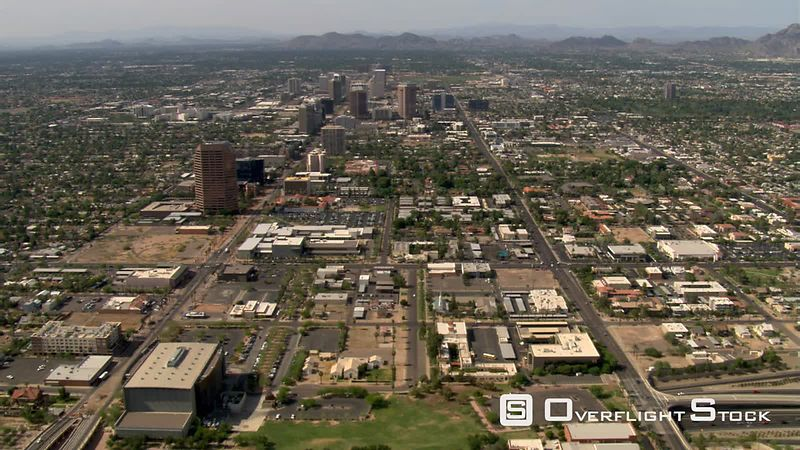 High aerial approach to Phoenix skyscrapers with mountains in background.
