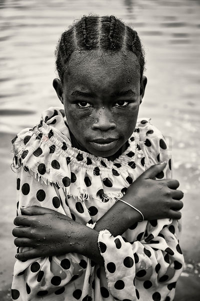 Portrait of a Young Girl Standing and Shivering in Flood Waters