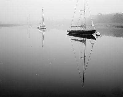 Moody misty scene on the Beaulieu River, with a mirror-like river reflecting the moored yachts and boats.