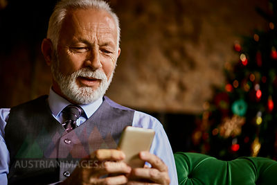 Elegant senior man using cell phone