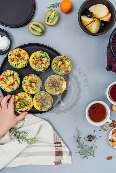 A kid grabbing a vegetarian breakfast omelet muffins from a black plate photographed from top view. Tea in tea cups, a teapot, fruit and cream accompany.