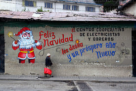Man walking past Father Christmas mural on wall of the offices of an electricians and electrical workers cooperative, La Paz, Bolivia