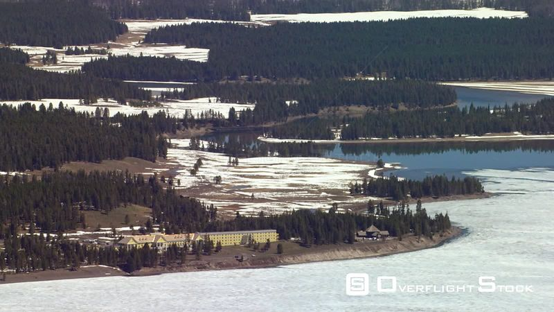 The Lake Hotel sits on the shore of the ice covered Yellowstone lake in the heart of Yellowstone National Park, with the Absaroka mountain range in the background