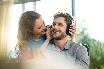 Smiling woman putting on headphones on boyfriend