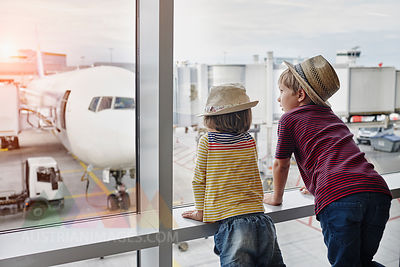 Two children wearing straw hats looking through window to airplane on the apron