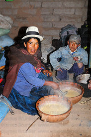Woman serving kalapurka in her adobe house , near Macha , Potosi Department , Bolivia