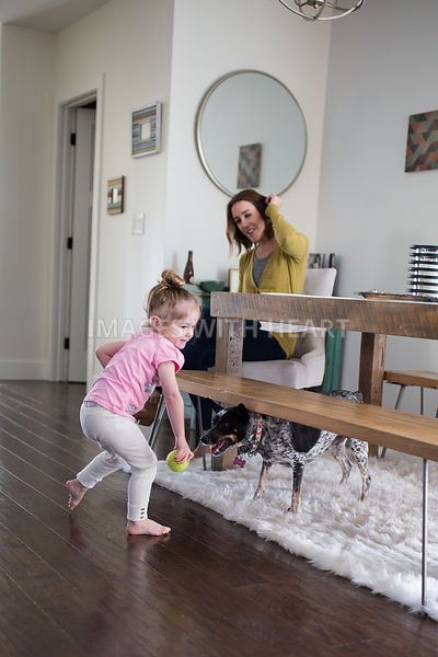 Little Girl and Woman Playing with Dog in Dining Room