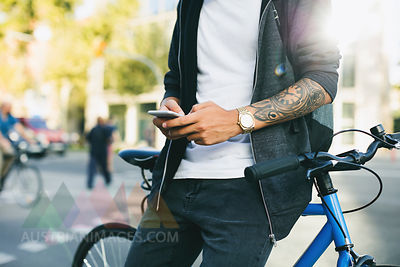 Teenager with a fixie bike, using smartphone