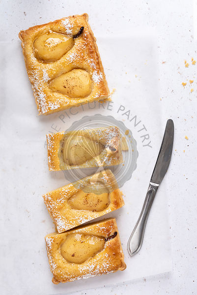 Rectangular glazed pear tart cut into pieces with a knife.