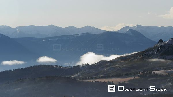 Snowcapped peaks and low hanging clouds at dawn with the Absaroka mountain Range in the background, in southwestern Montana