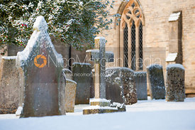 Snow covered grave stones in a sunny church yard
