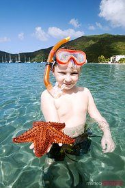 Child showing red starfish from tropical caribbean sea