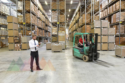 Businessman with laptop in warehouse and worker on forklift