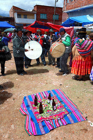 Musicians playing drums and flutes at festival, communal supply of beer and coca leaves in foreground, Caquiaviri, Bolivia