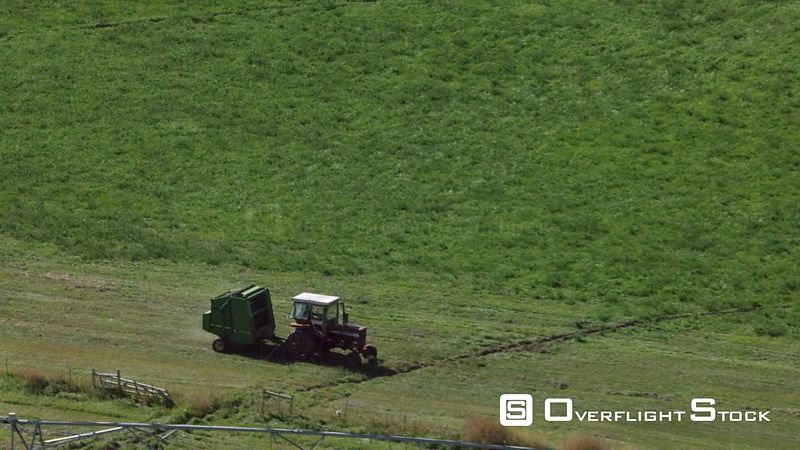 A red tractor pulls a hay bailer through a field in  the high desert of western Wyoming