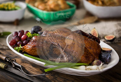 A platter of roast duck with a holiday meal in the background on a warm, rustic wood tabletop.