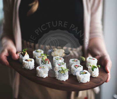 Sushi with pickled vegetables. Held by a woman.